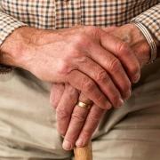 Elderly man holding walking stick